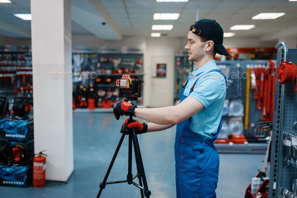 Worker testing laser level on tripod in tool store - Stock Photo - Images