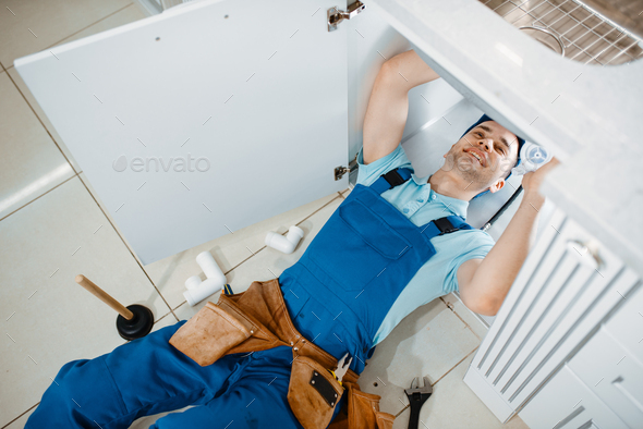 Plumber in uniform installing drain pipe, top view - Stock Photo - Images