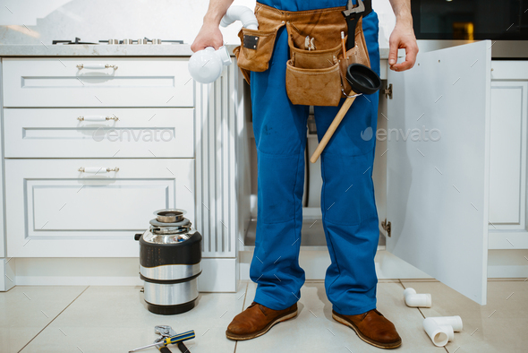 Male plumber installing water filter in kitchen - Stock Photo - Images