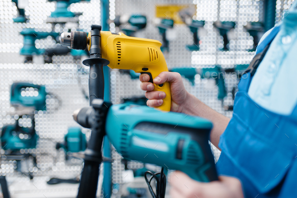 Worker holds two electric drills in tool store - Stock Photo - Images