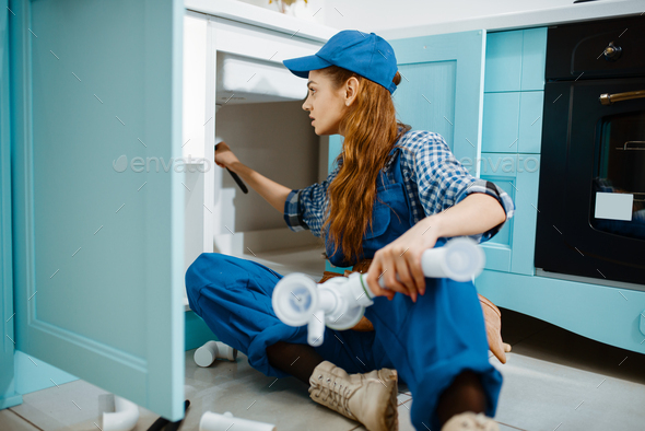 Female plumber fixing problem with drain pipe - Stock Photo - Images