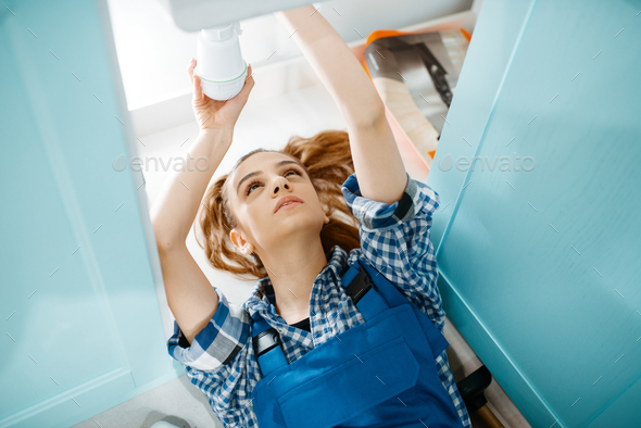 Female plumber lying on the floor, top view - Stock Photo - Images