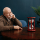 Elderly man looking on sandglass in home office - PhotoDune Item for Sale