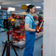 Worker testing laser level on tripod in tool store - PhotoDune Item for Sale