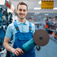 Male worker holds angle grinder in tool store - PhotoDune Item for Sale
