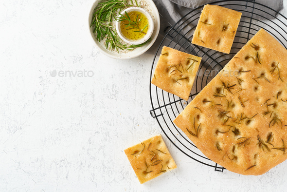Focaccia, pizza, italian flat bread with rosemary and olive oil on grid - Stock Photo - Images