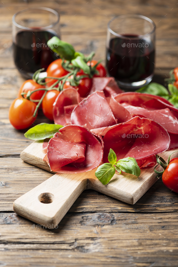 Italian antipasto with bresaola and red wine - Stock Photo - Images