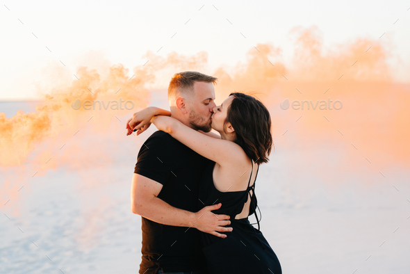 guy and a girl in black clothes hug and run on the white sand - Stock Photo - Images