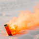 smoke bomb with orange smoke stuck in the sand - PhotoDune Item for Sale