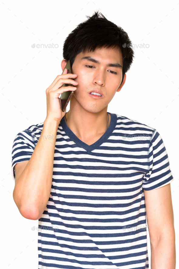 Studio shot of young handsome Asian man talking on mobile phone isolated against white background - Stock Photo - Images