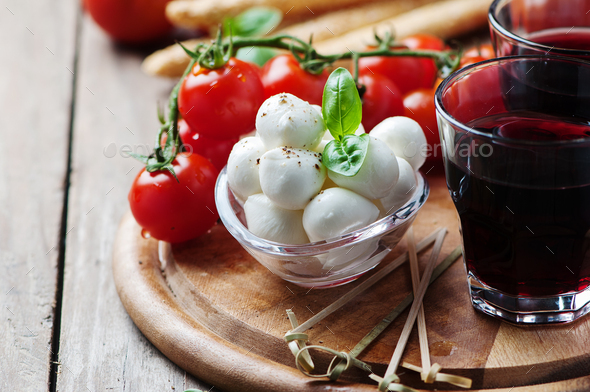 Mozzarella, tomato and basil on the wooden table - Stock Photo - Images