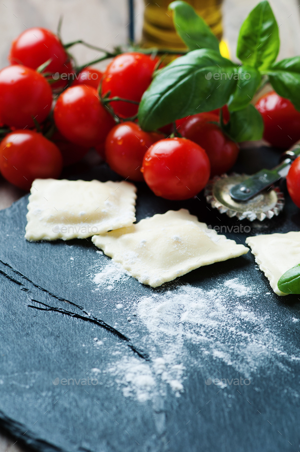 Uncooked ravioli with tomato and basil - Stock Photo - Images