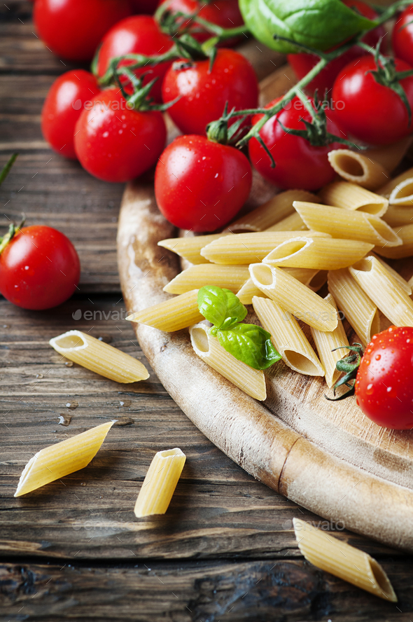Raw intergal pasta with fresh tomato and basil - Stock Photo - Images