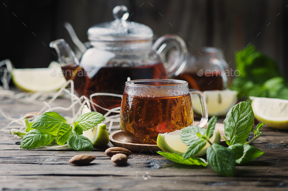 Hot black tea with lemon and mint on the wooden table - Stock Photo - Images