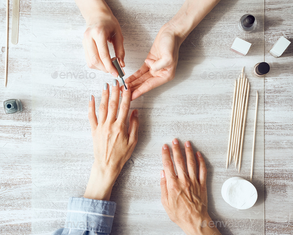 Mother and daughter do manicure, paint nails with varnish. Home self-care during quarantine - Stock Photo - Images