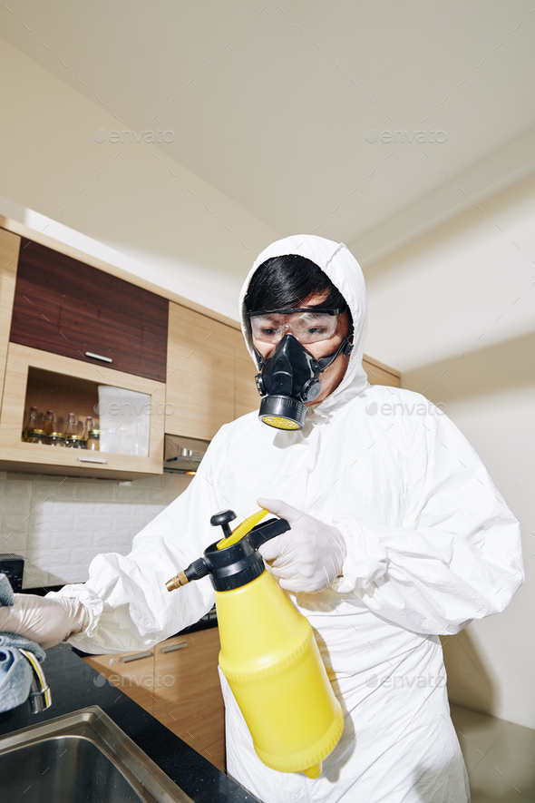 Worker spraying antiviral and antibacterial spay - Stock Photo - Images