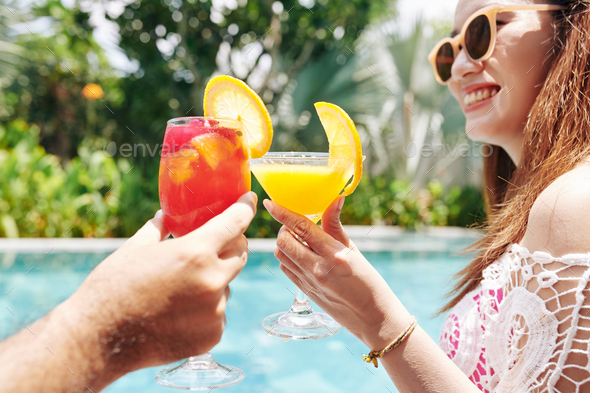 Happy woman drinking cocktail by pool - Stock Photo - Images