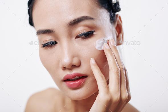 Woman applying moisturizer - Stock Photo - Images