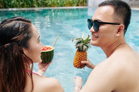 Boyfriend and girlfriend enjoying fruit ccktails - Stock Photo - Images