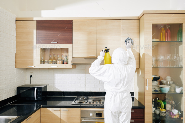 Worker wiping kitchen cabinets - Stock Photo - Images
