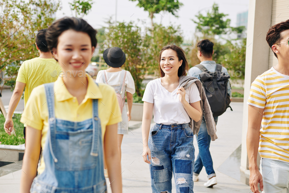 Young Asian woman walking outdoors - Stock Photo - Images