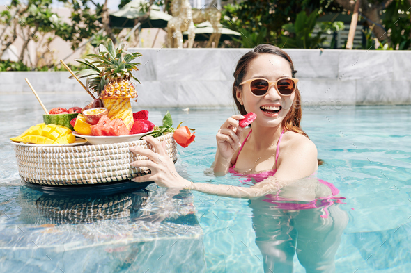 Woman enjoying tasty red passion fruit - Stock Photo - Images