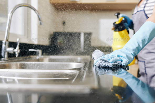 Woman disinfecting kitchen counter - Stock Photo - Images