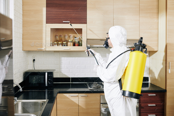 Worker in hazmat suit applying spray on surfaces - Stock Photo - Images