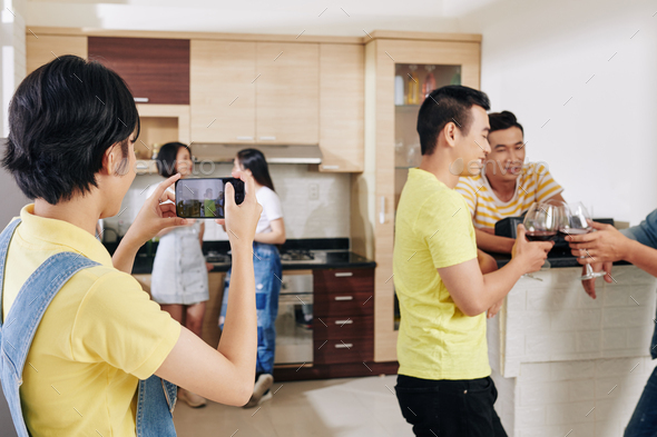 WOman photographing friewns at party - Stock Photo - Images