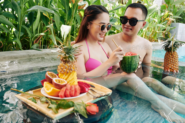 Smiling couple resting in small pool - Stock Photo - Images