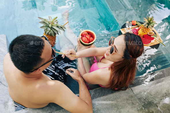 Couple eating fruits in swimming pool - Stock Photo - Images