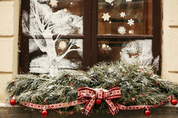 Stylish christmas snowy fir branches with festive red bow and balls on window store - Stock Photo - Images