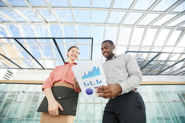 Successful Young Business People Discussing Documents under Glass Roof - Stock Photo - Images