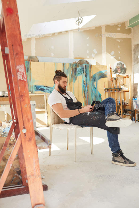 Contemporary Male Artist Using Smartphone in Workshop - Stock Photo - Images