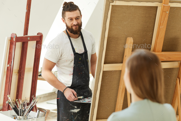 Smiling Male Artist Painting Portrait in Studio - Stock Photo - Images