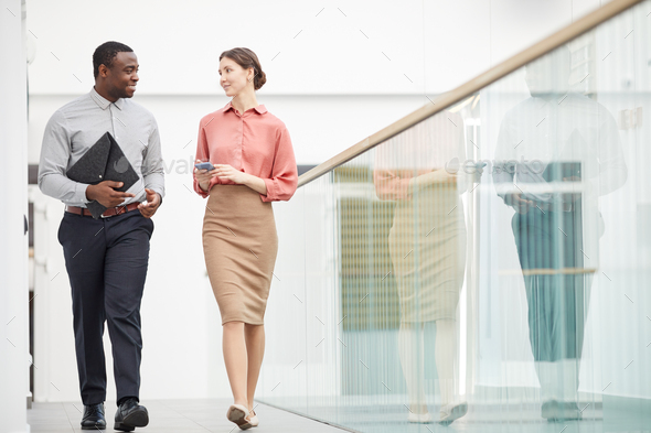 Two Business People Walking in Office Building - Stock Photo - Images