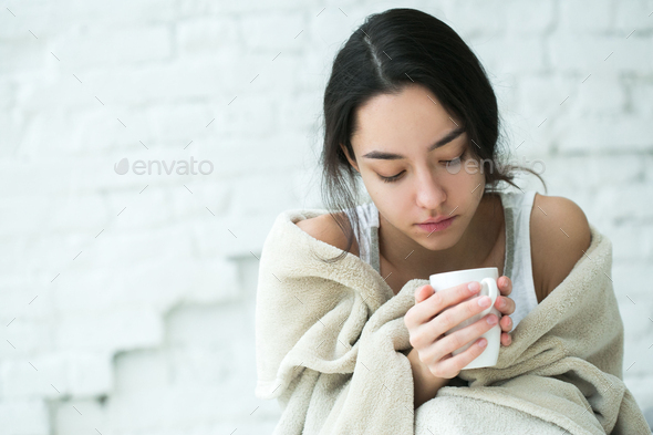 Young woman sick with temperature drinks hot - Stock Photo - Images