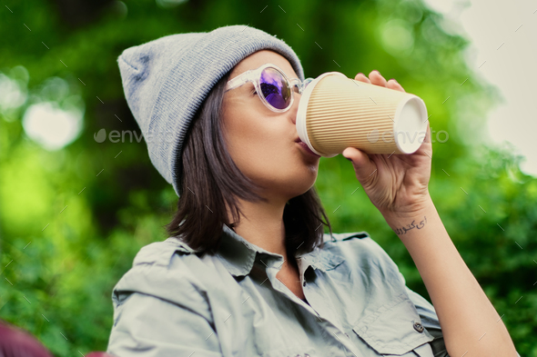 Female drinks coffee  in a summer park. - Stock Photo - Images