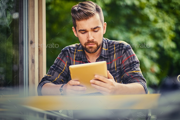 A man  using a tablet PC in a cafe on a street. - Stock Photo - Images