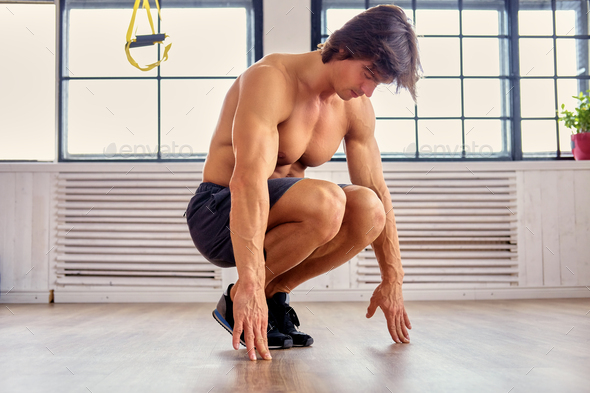 A man doing workouts on a floor in a room. - Stock Photo - Images