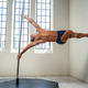 Man pole dancing in a hall with big windows. - PhotoDune Item for Sale