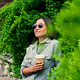 Brunette female in sunglasses drinks coffee in a summer park. - PhotoDune Item for Sale