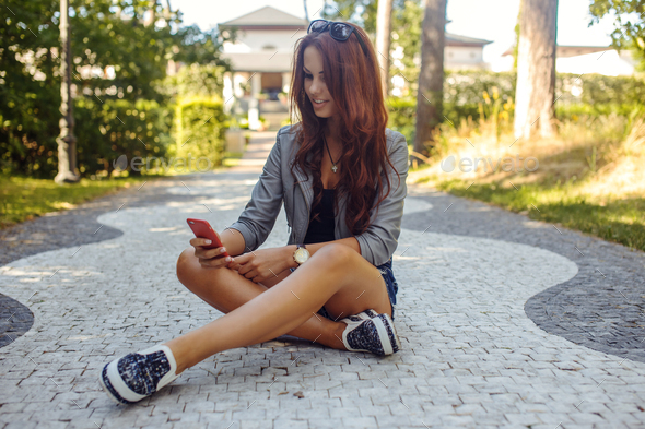 Sexy casual female sitting on the road. - Stock Photo - Images