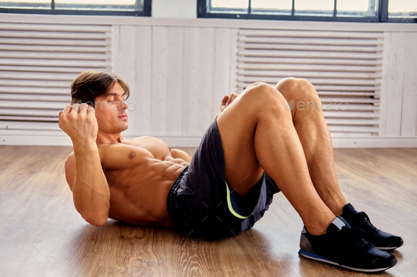 Shirtless male doing stomach workouts on a floor in a room. - Stock Photo - Images