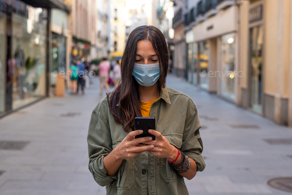 Woman on the street with mask and phone - Stock Photo - Images