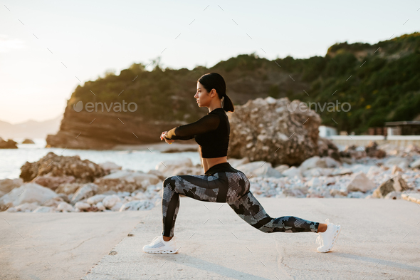 sexy athletic woman stretching exercises on beach at sunset - Stock Photo - Images