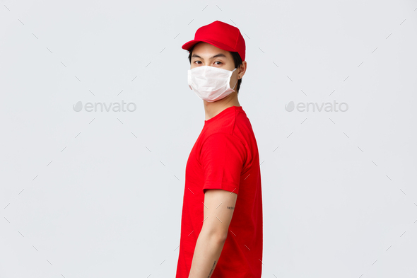 Portrait of asian delivery guy in red cap and t-shirt, wear protective medical mask, turn face to - Stock Photo - Images
