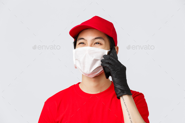 Covid-19, self-quarantine online shopping and delivery concept. Friendly young asian courier in - Stock Photo - Images