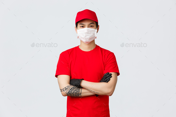 Confident young asian man in red delivery service uniform and cap, wearing protective medical mask - Stock Photo - Images
