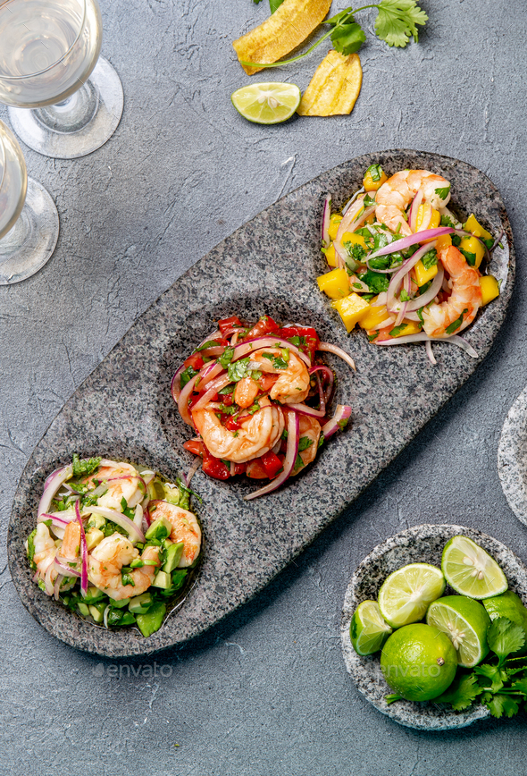 Three colorful shrimps ceviche with mango, avocado and tomatoes. - Stock Photo - Images